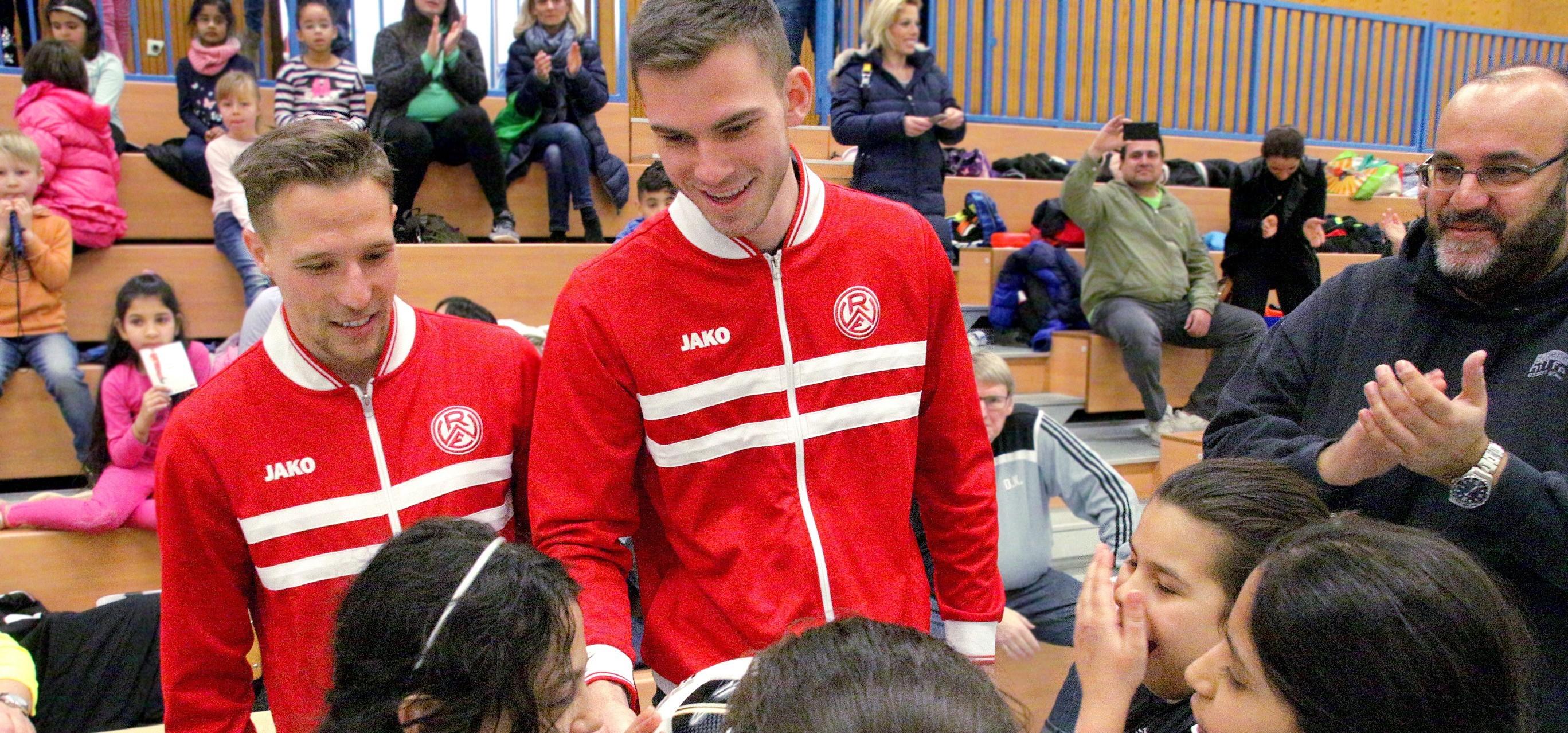 Herzlichen Glückwunsch! Die Rot-Weissen Florian Bichler (li.) und Boris Tomiak gratulieren dem Mädelsteam der Josefschule II mit einem signierten RWE-Ball. (Foto: Müller)