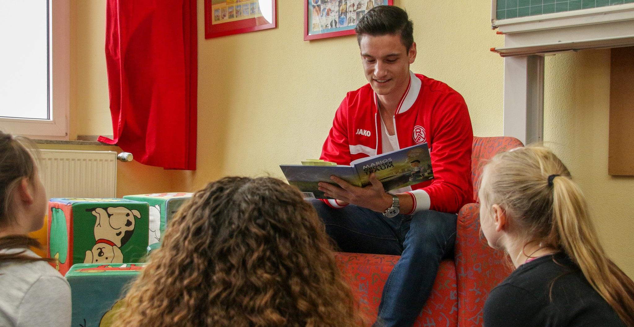 """Spannende Lesung für die Bergmühlenschüler: RWE-Spieler Noah Korczowski brachte das mehrfach ausgezeichnete Kinderbuch """"Marios großer Traum"""" zu Gehör. (Foto: Müller/EC)"""