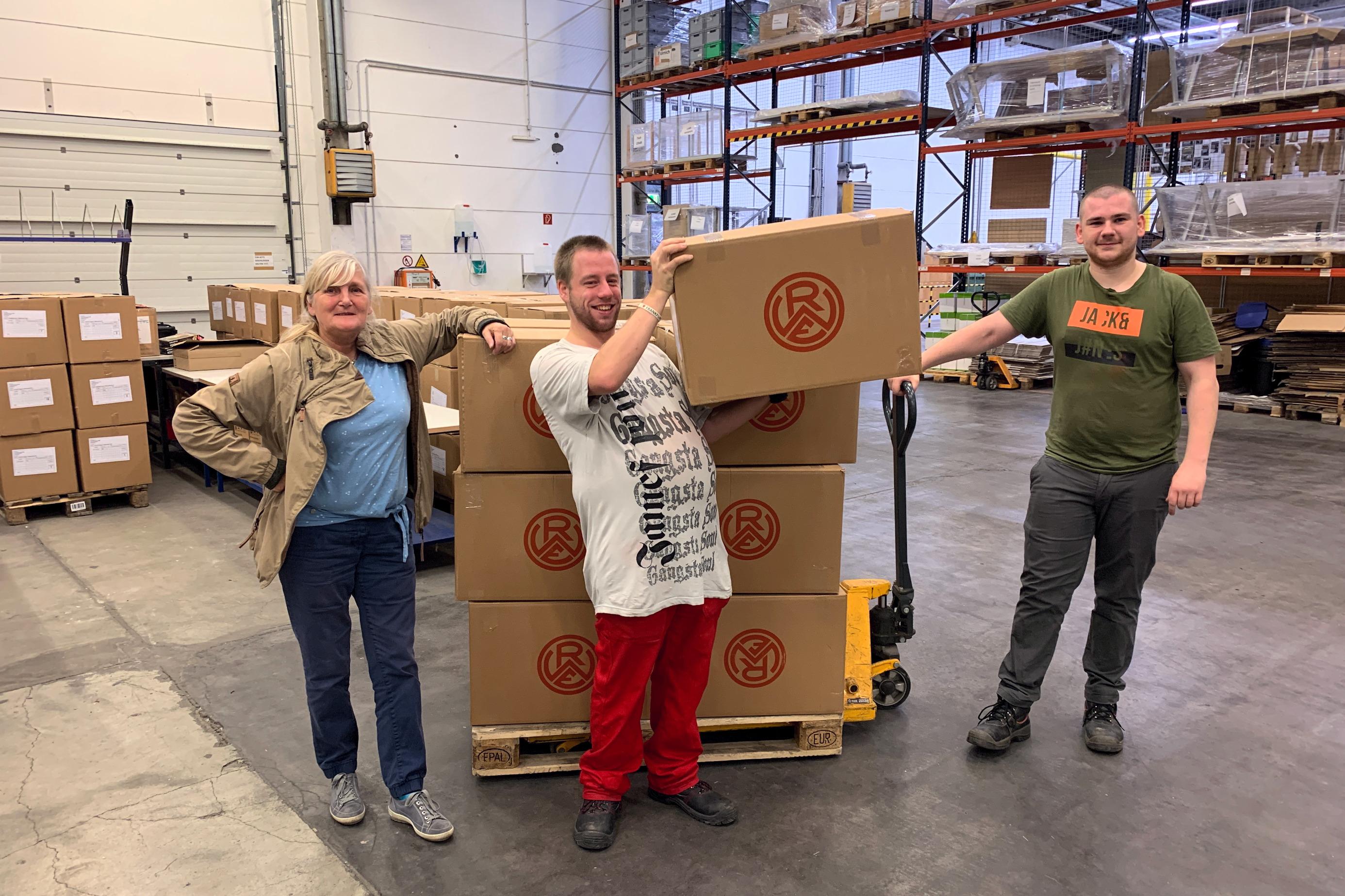Bildunterschrift 1: Arbeit unter realitätsnahen Bedingungen: Mit Unterstützung von Anleiterin Rosi Zweydorf (li.) haben die Jugendlichen die neue Hafenstreetwear von Rot-Weiss Essen kommissioniert. (Fotos: Capitain/JBH)