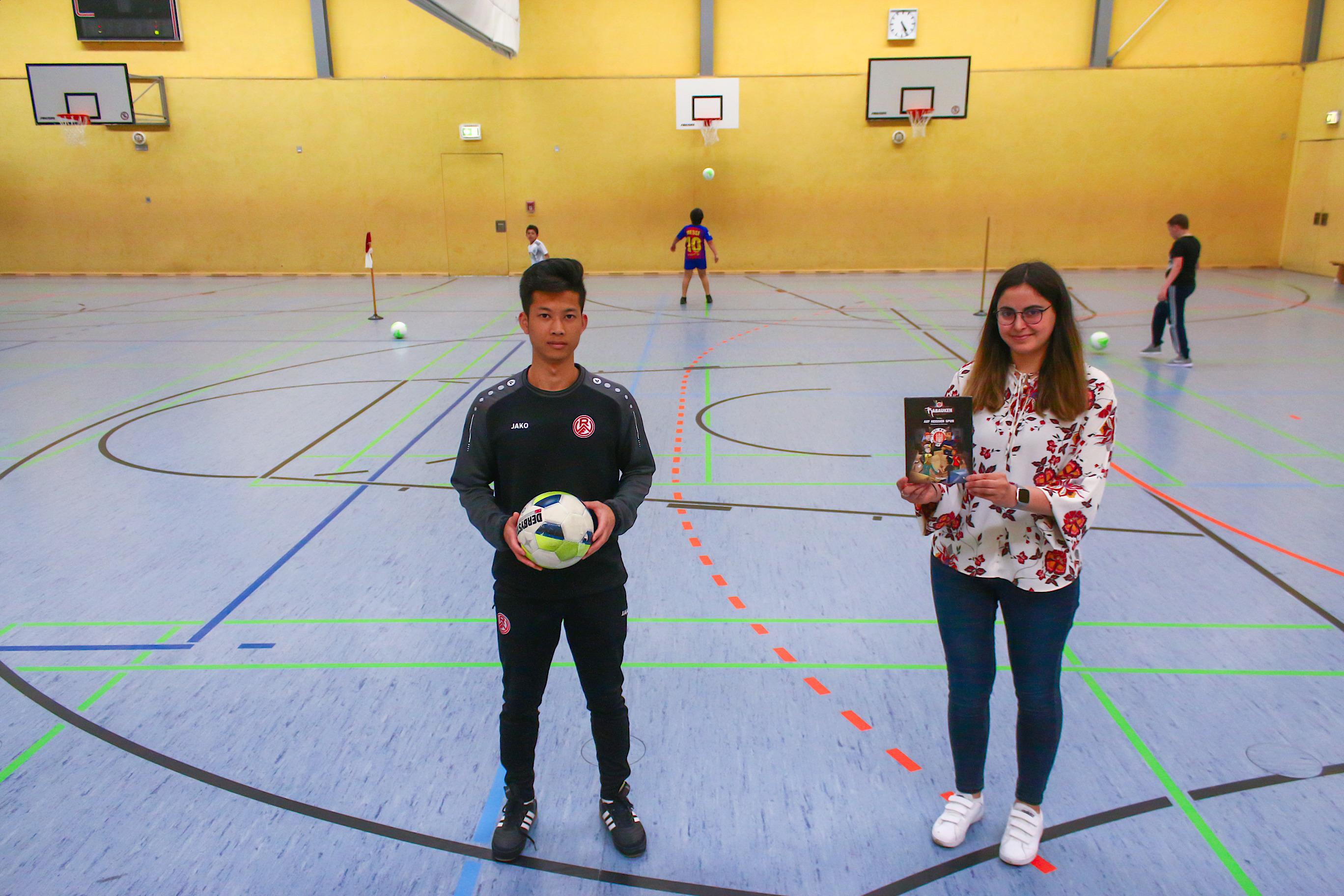 Kicken und Lernen in einer runden Kombi: RWE-Jugendtrainer Qiang Li (li.) und Fußball-trifft-Kultur-Lehrerin Büsra Sahin haben an der Gesamtschule Nord das Ferienprogramm für die Vogelheimer Kinder durchgeführt. Foto: Müller/EC