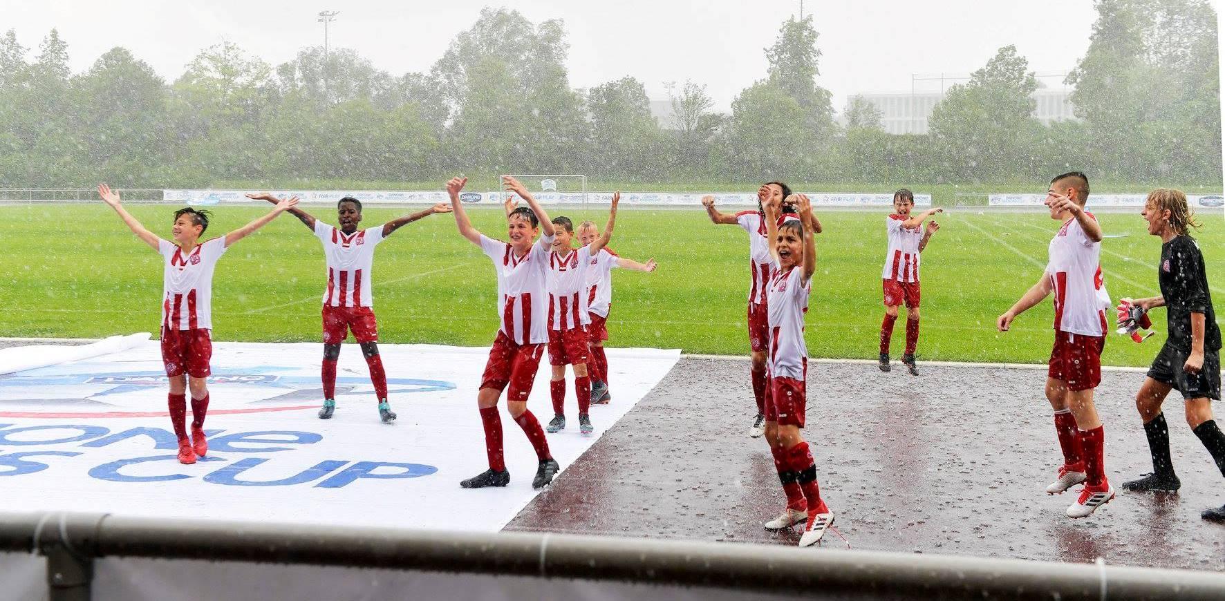 Freudentanz im Regen: Rot-Weiss Essens U12 feiert den Finalsieg und die Qualifikation für die Endrunde des Danone Nations Cups.