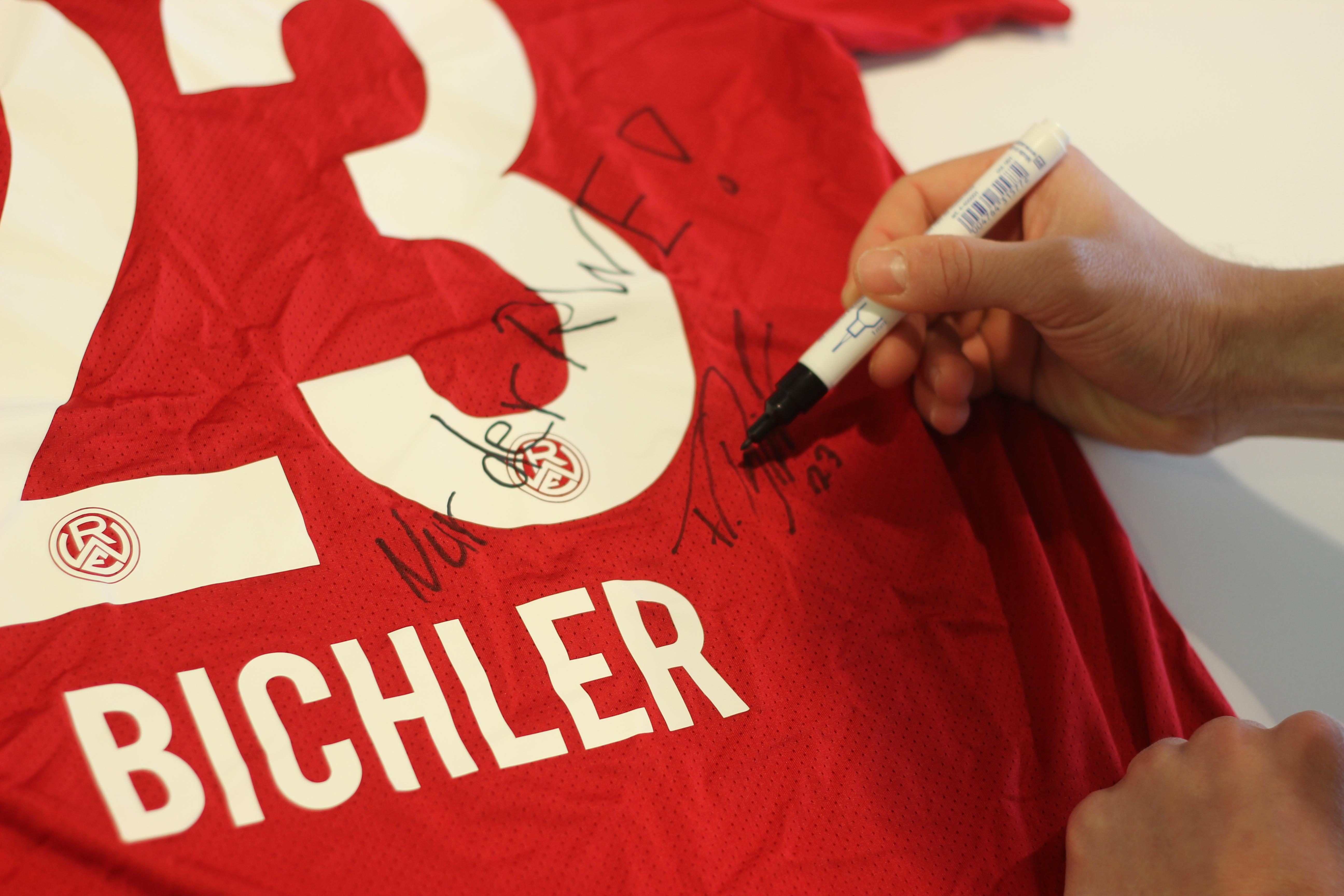 Florian Bichler signiert sein letztes RWE-Trikot.