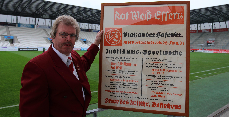 """RWE-Fan Andre Fabritz präsentiert das Plakat zur """"Jubiläums Sportwoche""""."""