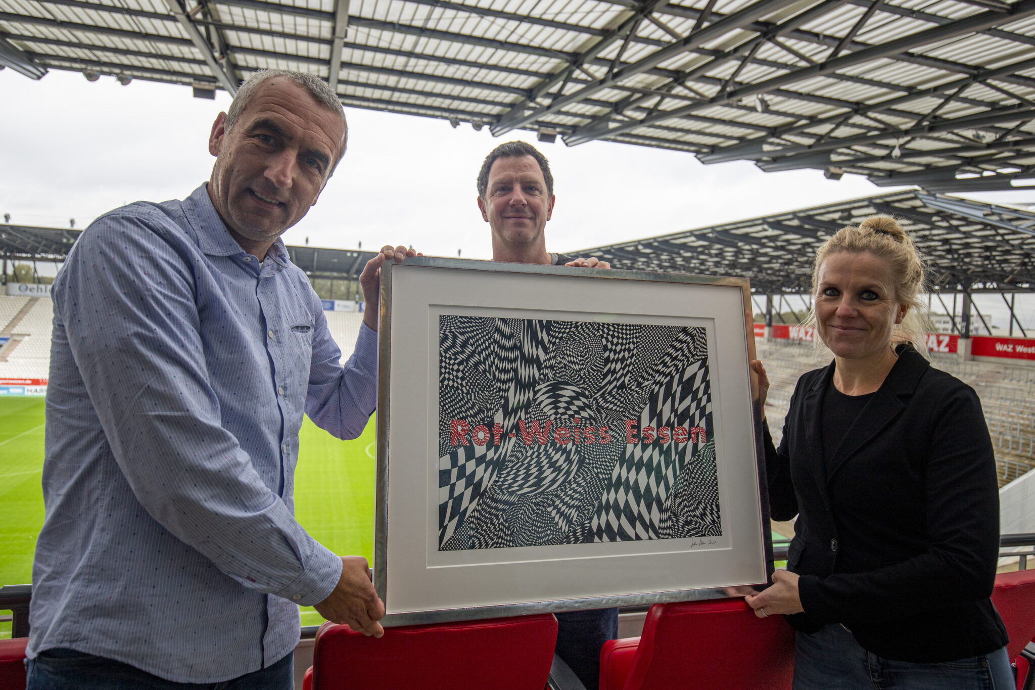 Marcus Uhlig, Tani Capitain und Julia Stärz halten das RWE-Kunstwerk hoch.