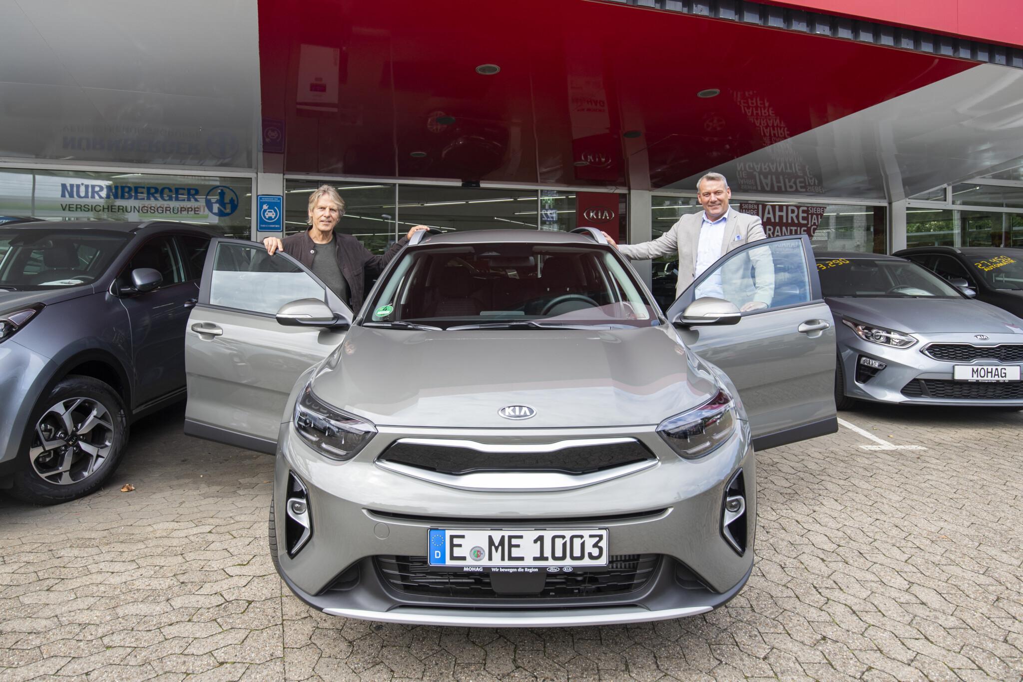 RWE-Marketingleiter Rainer Koch und MOHAG-Filialleiter Thomas Gudd stehen vor der Filiale und präsentieren einen Kia Stonic.