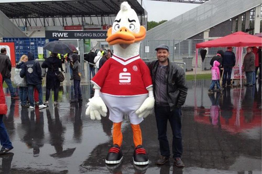 """RWE-Fan Oliver Kraaz mit Maskottchen """"Ente Willi"""" an der Hafenstraße."""